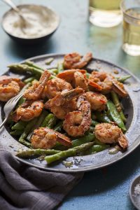 pan fried prawns with chilli, garlic and brandy on an asparagus and pea salad