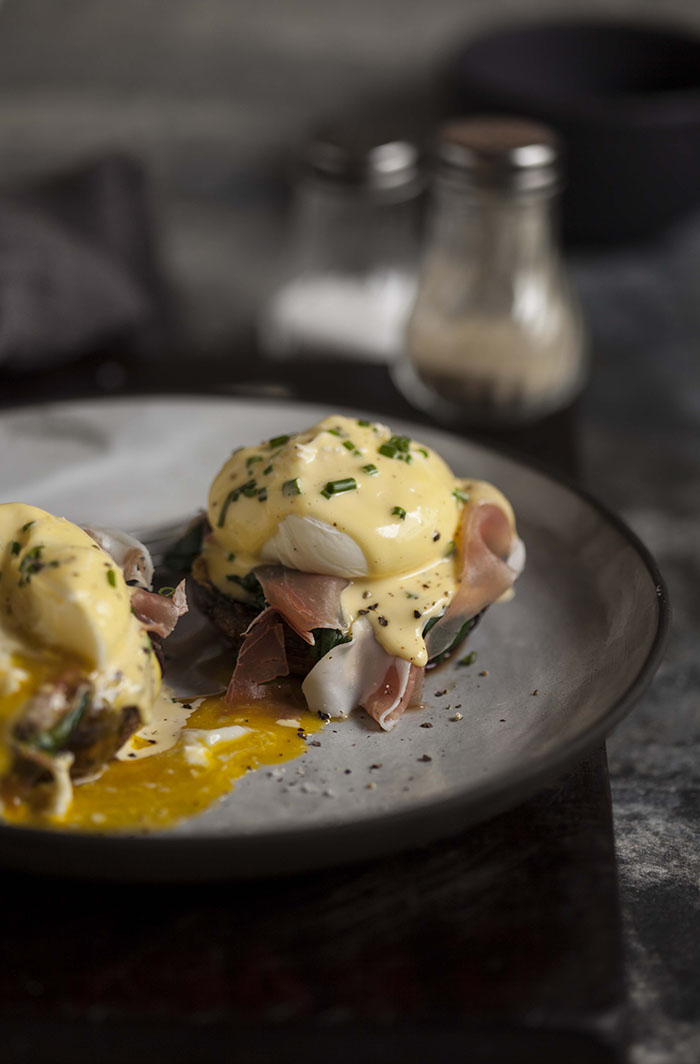 eggs benedict on roasted brown mushrooms spinach and prosciutto