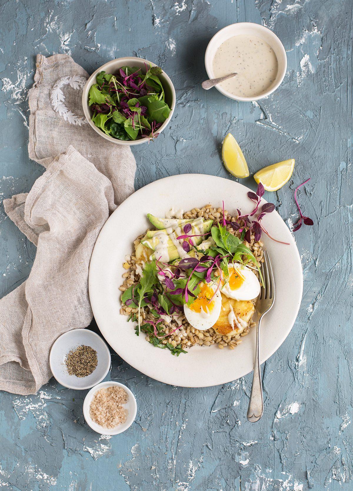barley breakfast bowl with halloumi, avocado, egg & tahini dressing