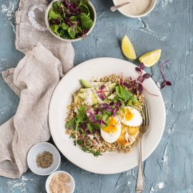 barley breakfast bowl with halloumi, avocado, egg & tahini dressing