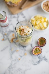 Tropical overnight oats recipe with pineapple, kiwi, passion fruit and toasted coconut shavings